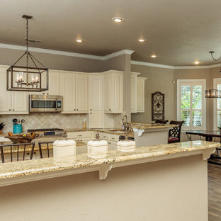 Large country galley eat-in kitchen in Dallas with raised-panel cabinets, white cabinets, granite benchtops, beige splashback, carpet, with island and brown floor.