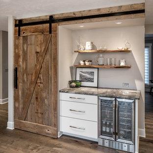 Bild på ett mellanstort lantligt flerfärgad flerfärgat kök, med släta luckor, vita skåp, granitbänkskiva, rostfria vitvaror, mellanmörkt trägolv, en köksö och brunt golv