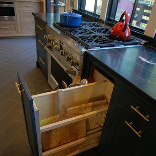 Modelo de cocina en L, industrial, de tamaño medio, con despensa, fregadero sobremueble, armarios con paneles lisos, puertas de armario grises, encimera de esteatita, electrodomésticos de acero inoxidable, suelo de baldosas de porcelana y una isla