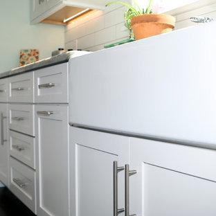 他の地域の大きいカントリー風おしゃれなキッチン (エプロンフロントシンク、シェーカースタイル扉のキャビネット、白いキャビネット、珪岩カウンター、白いキッチンパネル、緑のキッチンカウンター、シルバーの調理設備の、茶色い床) の写真