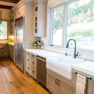 サンフランシスコの大きいカントリー風おしゃれなキッチン (エプロンフロントシンク、シェーカースタイル扉のキャビネット、グレーのキャビネット、コンクリートカウンター、グレーのキッチンパネル、サブウェイタイルのキッチンパネル、シルバーの調理設備の、無垢フローリング、ベージュの床、ベージュのキッチンカウンター) の写真