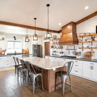 他の地域の大きいカントリー風おしゃれなキッチン (エプロンフロントシンク、シェーカースタイル扉のキャビネット、白いキャビネット、ラミネートカウンター、シルバーの調理設備の、無垢フローリング、茶色い床、白いキッチンカウンター、白いキッチンパネル) の写真