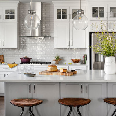 Inspiration for a large country l-shaped dark wood floor and brown floor eat-in kitchen remodel in DC Metro with a farmhouse sink, white cabinets, quartz countertops, white backsplash, subway tile backsplash, stainless steel appliances, an island, white countertops and shaker cabinets