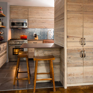 This is an example of a small transitional u-shaped eat-in kitchen in New York with a farmhouse sink, flat-panel cabinets, light wood cabinets, stainless steel appliances, ceramic floors, quartz benchtops, blue splashback, glass tile splashback and a peninsula.