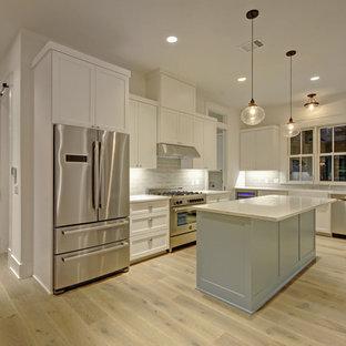 Exempel på ett mellanstort lantligt kök, med en rustik diskho, skåp i shakerstil, vita skåp, stänkskydd i keramik, rostfria vitvaror, laminatgolv, en köksö och beiget golv