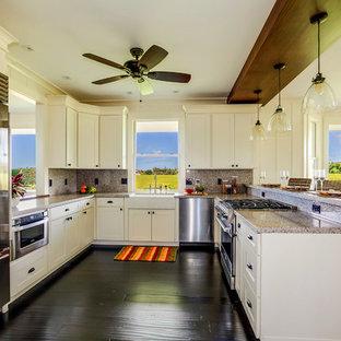 Идея дизайна: п-образная кухня-гостиная среднего размера в морском стиле с раковиной в стиле кантри, фасадами в стиле шейкер, белыми фасадами, гранитной столешницей, серым фартуком, фартуком из каменной плиты, техникой из нержавеющей стали, полом из бамбука, полуостровом и черным полом