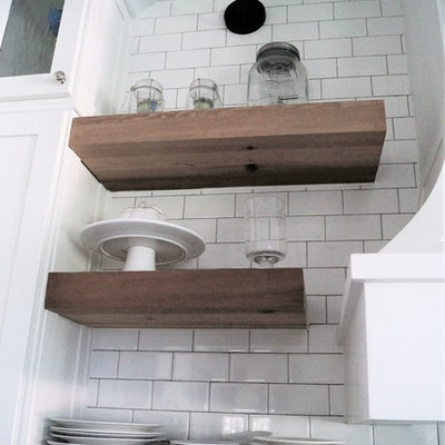 Example of a mid-sized cottage galley light wood floor and yellow floor open concept kitchen design in Other with a farmhouse sink, shaker cabinets, white cabinets, solid surface countertops, white backsplash, subway tile backsplash, stainless steel appliances, an island and black countertops