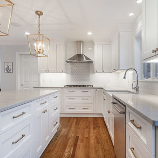 Design ideas for a large farmhouse l-shaped open plan kitchen in DC Metro with a belfast sink, shaker cabinets, white cabinets, engineered stone countertops, white splashback, ceramic splashback, stainless steel appliances, medium hardwood flooring, an island, brown floors and yellow worktops.