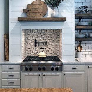 Ejemplo de cocina campestre con salpicadero de piedra caliza y una isla