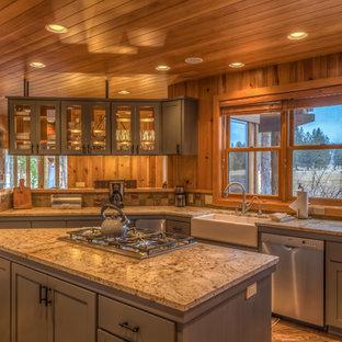 他の地域の大きいサンタフェスタイルのおしゃれなキッチン (エプロンフロントシンク、シェーカースタイル扉のキャビネット、グレーのキャビネット、御影石カウンター、マルチカラーのキッチンパネル、石タイルのキッチンパネル、シルバーの調理設備の、淡色無垢フローリング、茶色い床) の写真