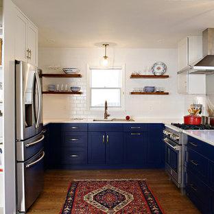 Immagine di una cucina ad U classica con lavello sottopiano, ante in stile shaker, ante blu, top in quarzo composito, paraspruzzi bianco, paraspruzzi con piastrelle diamantate, elettrodomestici in acciaio inossidabile, pavimento in legno massello medio e nessuna isola