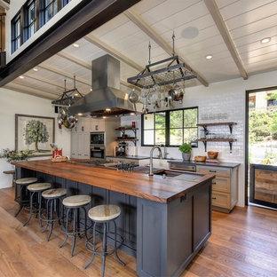 サクラメントのトランジショナルスタイルのおしゃれなアイランドキッチン (エプロンフロントシンク、シェーカースタイル扉のキャビネット、グレーのキャビネット、木材カウンター、白いキッチンパネル、無垢フローリング) の写真
