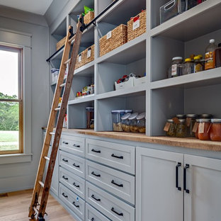 ナッシュビルの大きいカントリー風おしゃれなキッチン (木材カウンター、エプロンフロントシンク、シェーカースタイル扉のキャビネット、白いキャビネット、白いキッチンパネル、サブウェイタイルのキッチンパネル、シルバーの調理設備の、無垢フローリング、茶色い床、白いキッチンカウンター) の写真