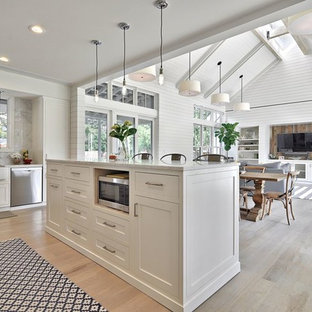Inspiration for a country open plan kitchen in Austin with a farmhouse sink, shaker cabinets, white cabinets, marble benchtops, white splashback, stone slab splashback, stainless steel appliances and light hardwood floors.