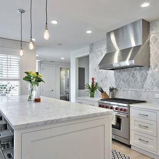 Example of a cottage kitchen design in Austin with a farmhouse sink, shaker cabinets, white cabinets, marble countertops, gray backsplash, stone tile backsplash and stainless steel appliances