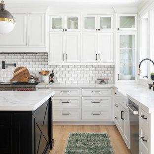 На фото: большая п-образная кухня в стиле кантри с раковиной в стиле кантри, фасадами в стиле шейкер, белыми фасадами, столешницей из кварцевого агломерата, белым фартуком, фартуком из плитки кабанчик, светлым паркетным полом, двумя и более островами и белой столешницей с