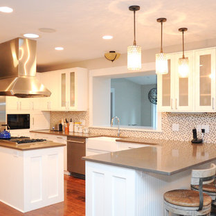 Transitional u-shaped kitchen photo in St Louis with a farmhouse sink, shaker cabinets, white cabinets, multicolored backsplash and stainless steel appliances