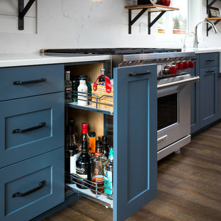 Medium sized country single-wall kitchen pantry in Portland with a belfast sink, shaker cabinets, grey cabinets, engineered stone countertops, stainless steel appliances, medium hardwood flooring, an island, brown floors, white splashback and stone tiled splashback.