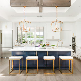 Large farmhouse eat-in kitchen designs - Inspiration for a large cottage u-shaped light wood floor and gray floor eat-in kitchen remodel in San Francisco with shaker cabinets, blue cabinets, white backsplash, an island, white countertops, a farmhouse sink, quartz countertops, ceramic backsplash and stainless steel appliances