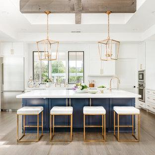 Große Landhaus Wohnküche in U-Form mit Schrankfronten im Shaker-Stil, blauen Schränken, Küchenrückwand in Weiß, hellem Holzboden, Kücheninsel, weißer Arbeitsplatte, Landhausspüle, Quarzwerkstein-Arbeitsplatte, Rückwand aus Keramikfliesen, Küchengeräten aus Edelstahl und grauem Boden in San Francisco