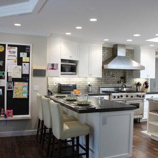 サンディエゴの大きいカントリー風おしゃれなキッチン (エプロンフロントシンク、シェーカースタイル扉のキャビネット、白いキャビネット、珪岩カウンター、ベージュキッチンパネル、テラコッタタイルのキッチンパネル、シルバーの調理設備の、濃色無垢フローリング) の写真
