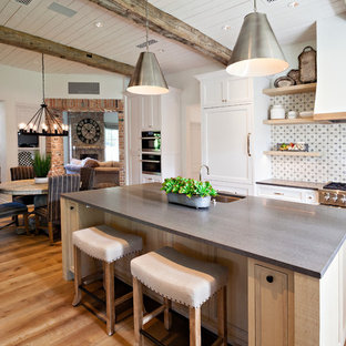 Farmhouse open concept kitchen designs - Inspiration for a cottage medium tone wood floor open concept kitchen remodel in Phoenix with an undermount sink, recessed-panel cabinets, white cabinets, multicolored backsplash, stainless steel appliances, an island and gray countertops