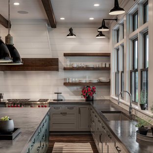 This is an example of a large country u-shaped eat-in kitchen in New York with a single-bowl sink, shaker cabinets, grey cabinets, concrete benchtops, white splashback, timber splashback, stainless steel appliances, dark hardwood floors, with island, brown floor and black benchtop.