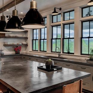 Idee per una grande cucina country con lavello a vasca singola, ante in stile shaker, ante grigie, top in cemento, paraspruzzi bianco, paraspruzzi in legno, elettrodomestici in acciaio inossidabile, parquet scuro, isola, pavimento marrone e top nero