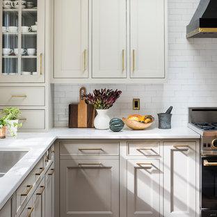ニューヨークの広いカントリー風おしゃれなキッチン (ダブルシンク、シェーカースタイル扉のキャビネット、ベージュのキャビネット、クオーツストーンカウンター、白いキッチンパネル、セラミックタイルのキッチンパネル、黒い調理設備、無垢フローリング、茶色い床、白いキッチンカウンター) の写真