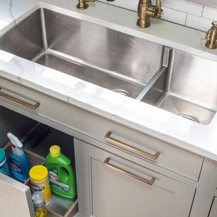 Foto på ett stort lantligt vit kök, med en dubbel diskho, skåp i shakerstil, beige skåp, bänkskiva i kvarts, vitt stänkskydd, stänkskydd i keramik, svarta vitvaror, mellanmörkt trägolv, en köksö och brunt golv