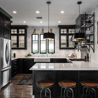 Exempel på ett avskilt, mellanstort lantligt grå grått u-kök, med en rustik diskho, rostfria vitvaror, en halv köksö, brunt golv, luckor med glaspanel, svarta skåp, grått stänkskydd, stänkskydd i tunnelbanekakel, ljust trägolv och bänkskiva i kvarts