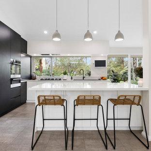 Modern inredning av ett stort kök, med en dubbel diskho, vita skåp, bänkskiva i kvarts, svarta vitvaror, klinkergolv i terrakotta och en köksö