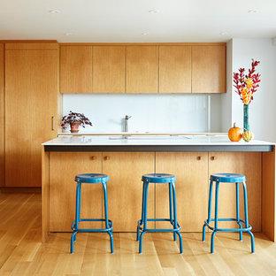 ニューヨークの中くらいのコンテンポラリースタイルのおしゃれなキッチン (フラットパネル扉のキャビネット、淡色木目調キャビネット、白いキッチンパネル、シルバーの調理設備、淡色無垢フローリング、アンダーカウンターシンク、人工大理石カウンター、ガラス板のキッチンパネル) の写真