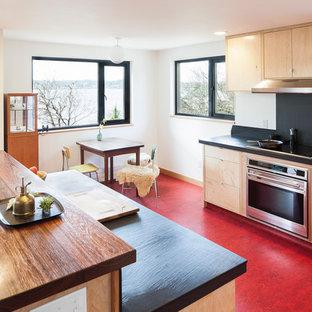 シアトルのモダンスタイルのおしゃれなキッチン (木材カウンター、赤い床) の写真