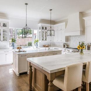 Foto di una cucina tradizionale con lavello stile country, ante in stile shaker, ante bianche, paraspruzzi bianco, elettrodomestici da incasso, parquet scuro, 2 o più isole e top bianco