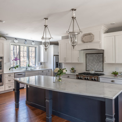 Example of a large classic l-shaped medium tone wood floor open concept kitchen design in Other with an undermount sink, recessed-panel cabinets, white cabinets, solid surface countertops, multicolored backsplash, ceramic backsplash, stainless steel appliances, an island and white countertops