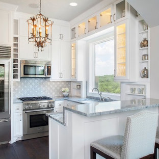 Small traditional kitchen appliance - Kitchen - small traditional u-shaped dark wood floor kitchen idea in Austin with an undermount sink, glass-front cabinets, white cabinets, multicolored backsplash, stainless steel appliances and a peninsula