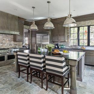 Inredning av ett rustikt mellanstort kök, med en undermonterad diskho, luckor med infälld panel, flerfärgad stänkskydd, rostfria vitvaror, en köksö, skåp i mörkt trä, stänkskydd i stenkakel, travertin golv och grått golv
