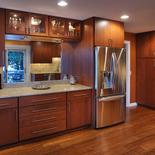 Inspiration for a modern u-shaped medium tone wood floor eat-in kitchen remodel in Nashville with an undermount sink, medium tone wood cabinets, granite countertops, stainless steel appliances and a peninsula