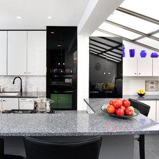 Bild på ett mellanstort funkis kök, med en undermonterad diskho, släta luckor, vita skåp, grått stänkskydd, stänkskydd i stickkakel, svarta vitvaror, en halv köksö, bänkskiva i kvarts och klinkergolv i porslin