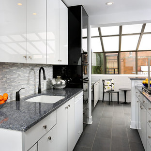 Small trendy galley porcelain floor enclosed kitchen photo in Chicago with an undermount sink, flat-panel cabinets, white cabinets, gray backsplash, matchstick tile backsplash, black appliances, no island and quartz countertops