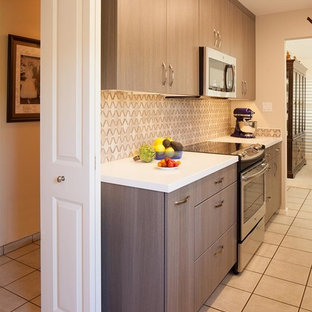 This is an example of a small modern galley separate kitchen in San Francisco with an undermount sink, flat-panel cabinets, dark wood cabinets, solid surface benchtops, beige splashback, stone tile splashback, panelled appliances, ceramic floors and no island.