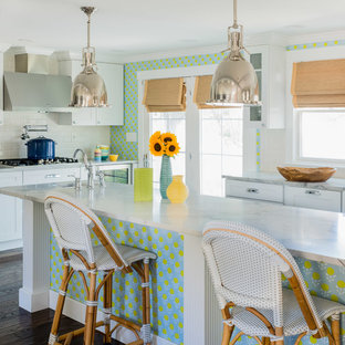 Beach style kitchen inspiration - Example of a coastal l-shaped dark wood floor and brown floor kitchen design in Boston with shaker cabinets, white cabinets, white backsplash, subway tile backsplash, white appliances, an island and white countertops