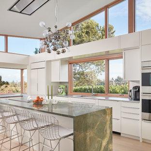 シアトルのコンテンポラリースタイルのおしゃれなキッチン (フラットパネル扉のキャビネット、白いキャビネット、ガラスまたは窓のキッチンパネル、シルバーの調理設備の、無垢フローリング、茶色い床、緑のキッチンカウンター) の写真