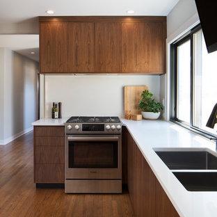 ミルウォーキーの中サイズのモダンスタイルのおしゃれなキッチン (アンダーカウンターシンク、フラットパネル扉のキャビネット、茶色いキャビネット、クオーツストーンカウンター、白いキッチンパネル、石スラブのキッチンパネル、シルバーの調理設備の、無垢フローリング、アイランドなし、赤い床) の写真
