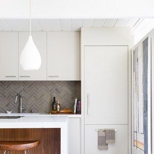 This is an example of a midcentury single-wall kitchen in San Francisco with an integrated sink, flat-panel cabinets, white cabinets, grey splashback, ceramic splashback, white appliances, concrete floors, with island and quartz benchtops.