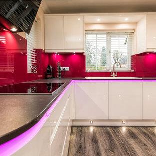 ハンプシャーの大きいモダンスタイルのおしゃれなキッチン (一体型シンク、フラットパネル扉のキャビネット、白いキャビネット、ピンクのキッチンパネル、ガラス板のキッチンパネル、シルバーの調理設備の、茶色い床、黒いキッチンカウンター) の写真