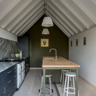 Inspiration for a farmhouse kitchen in Sussex with a submerged sink, blue cabinets, wood worktops, grey splashback, white appliances, light hardwood flooring and an island.