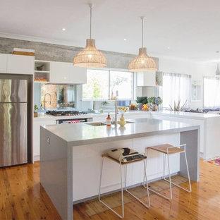 Mittelgroße Moderne Wohnküche in L-Form mit Unterbauwaschbecken, flächenbündigen Schrankfronten, weißen Schränken, Arbeitsplatte aus Recyclingglas, Rückwand aus Spiegelfliesen, Küchengeräten aus Edelstahl, braunem Holzboden und Kücheninsel in Miami