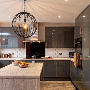 オックスフォードシャーの大きいコンテンポラリースタイルのおしゃれなキッチン (フラットパネル扉のキャビネット、グレーのキャビネット、木材カウンター、白いキッチンパネル、サブウェイタイルのキッチンパネル、シルバーの調理設備、無垢フローリング、ベージュの床、ベージュのキッチンカウンター) の写真